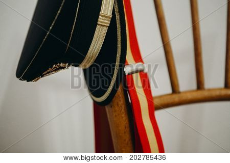 Spanish army cap and spanish flag suspenders in a chair
