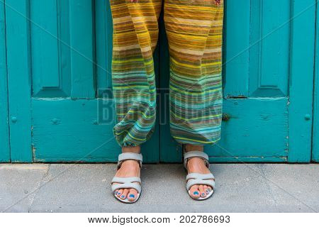 Feet Of A Woman In Sandals. Colorful Hippie Pants