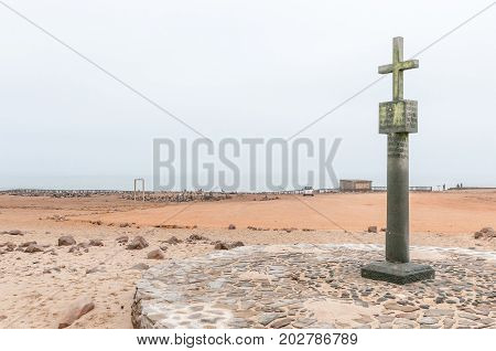CAPE CROSS NAMIBIA - JUNE 29 2017: A replica of the cross planted by Diogo Cao at Cape Cross with a seal colony in the back