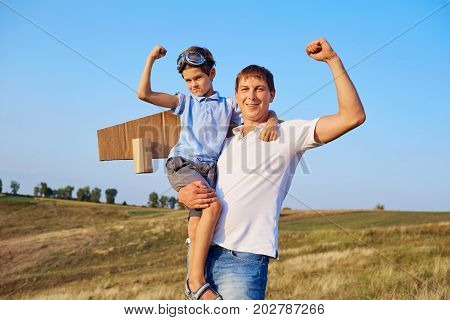 Father and son show muscles in nature.Father's Day.