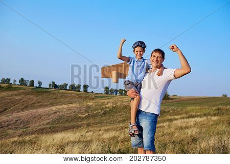 Father and son show muscles in nature. Father's Day.