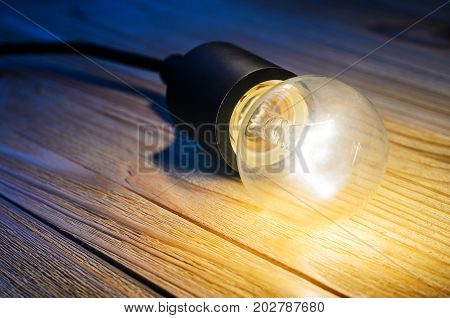 One burning incandescent bulb on a wooden table. Background with an empty space for your text