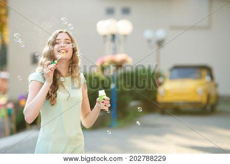 happy beautiful woman blowing soap bubbles outdoor. focus on soap bubbles