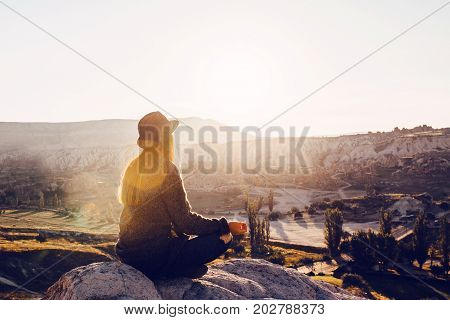 Young beautiful girl practicing yoga at the top of a mountain at sunrise.