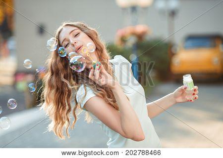 happy beautiful woman blowing soap bubbles outdoor
