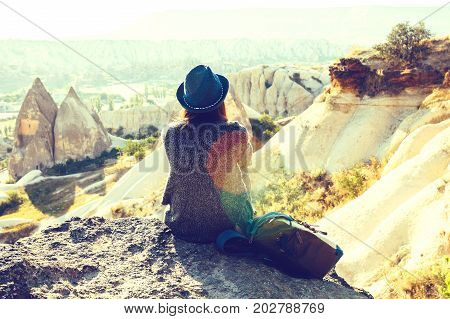 A traveler in a hat with a backpack stands on a mountain and looks at a beautiful view in Cappadocia in Turkey. Hiking.