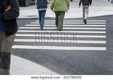 People cross the road on a pedestrian crossing.
