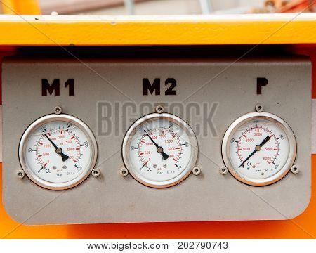 Three pressure gauges on yellow truck industry detail