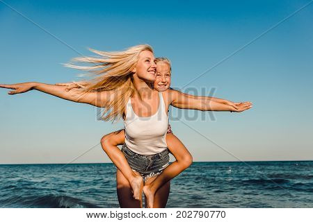 Happy family during summer vacation on against the sea ocean on a summer day. Mother and daughter on the beach