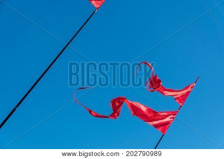 Red flags are fluttering in the wind against the blue sky.