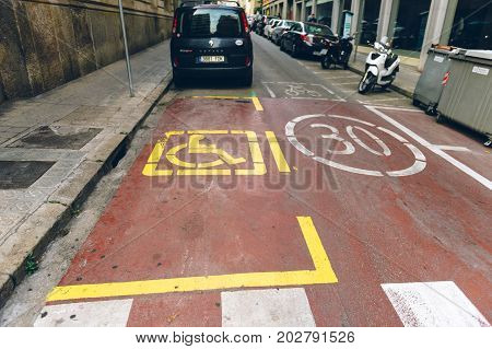 BARCELONA SPAIN JUN 29 2016: Disabled parking sign next to 30 km zone in urban enviroment Barcelona Spain street