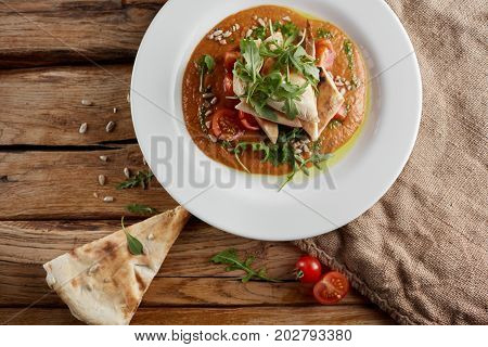 View of delicious italian soup for vegetarians, red gazpacho with tomato, basil, onion and raw vegetables. Tasty raw food on white plate with piece of pizza, little tomats cherry at wooden background.