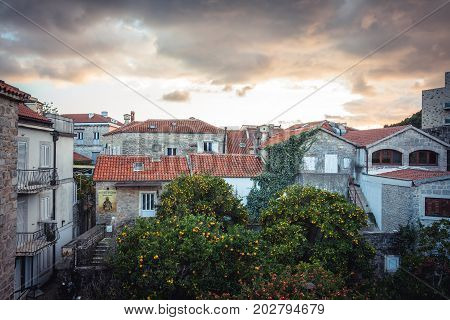 Old European city skyline with orange tile roofs in antique architecture among city park with trees in old European town Budva in Montenegro in front of dramatic sky during sunset