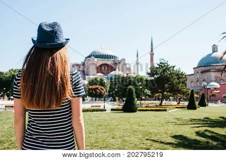 A young girl traveler in a hat from the back in Sultanahmet Square next to the famous Aya Sofia mosque in Istanbul, Turkey. Travel, tourism.