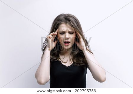 Woman puts hands on the head. Concept of problems and headache