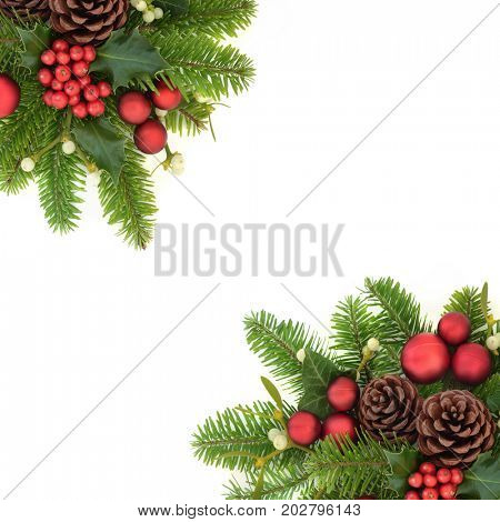 Decorative christmas background border with holly ivy, mistletoe, fir, red bauble decorations and pine cones on white.