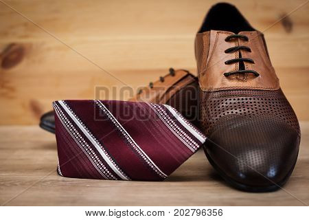 Man's style. Male shoes and tie in wooden background