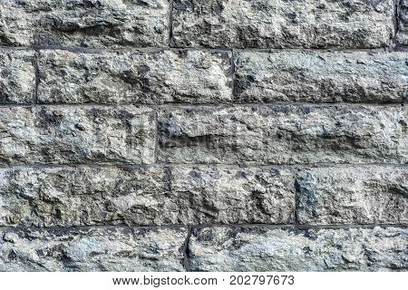 The image of a fragment of masonry wall of rough gray rough stone to use as a background.