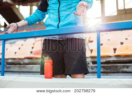 Indignant Sportsman With Bottle Of Water Standing Near Railing