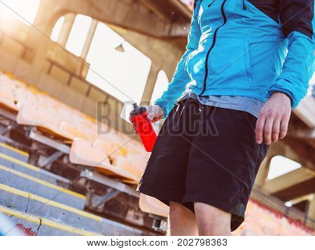 Sportsman With Red Bottle Of Water Standing On The Track And Field Stadium
