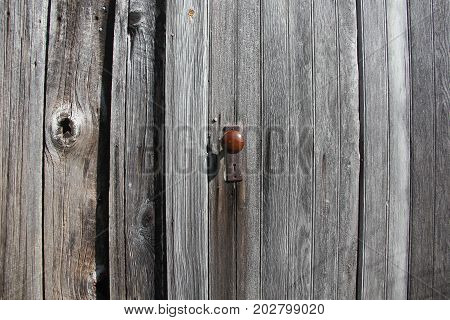 A wooden door closed on an old barn