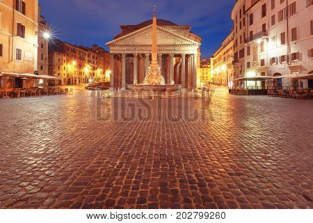 The Pantheon, former Roman temple of all gods, now a church, and Fountain with obelisk at Piazza della Rotonda, at night, Rome, Italy