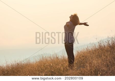 Happy woman enjoying the beautiful nature feel free and rising her arms while standing toward the setting sun. Lifestyle and freedom concept.