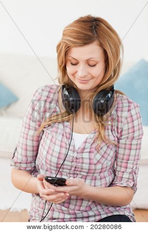 Blonde woman with headphones and mp3 player sitting in the living-room