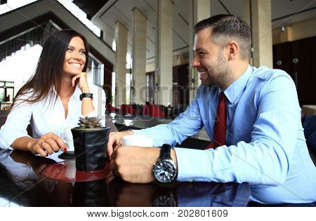 Happy business colleagues in modern office. Team of successful business people having a meeting in executive. Couple in modern cafe enjoying time together