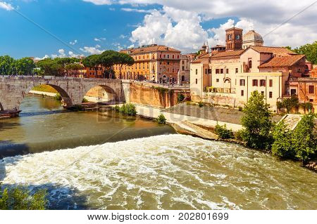 View of the Tiber island or Isola Tiberina with Pons Cestius and Basilica of St Bartholomew in sunny day, Rome, Italy