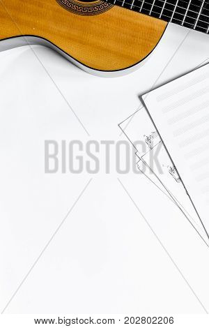 guitar with blank paper in music studio for dj or musician work on white desk background top view mock-up