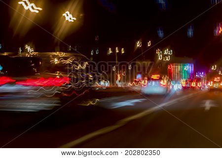 Urban street night traffic with bokeh lights. Blurred auto with bright brake lights, city street lights and speed. Abstract coloful blurred background. Selective focus.