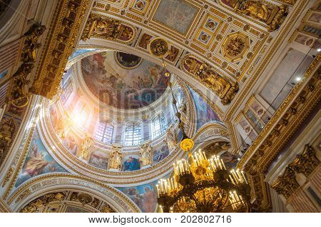 SAINT PETERSBURG RUSSIA - AUGUST 15 2017. Ceiling ornated with sculptures and Bible paintings in the interior of the St Isaac Cathedral in Saint Petersburg Russia. Saint Petersburg Russia landmark