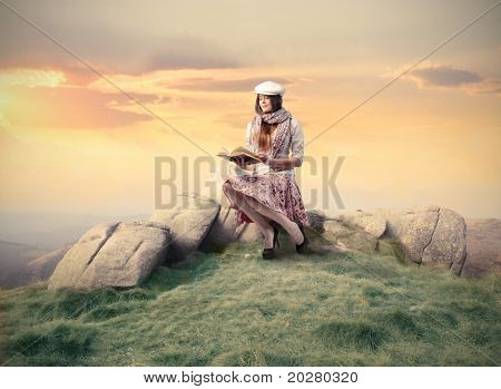 Elegant woman sitting on a stone and reading a book