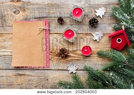 toys, candles and notebook to decorate christmas tree for new year celebration with fur tree branches on wooden table background top veiw mockup