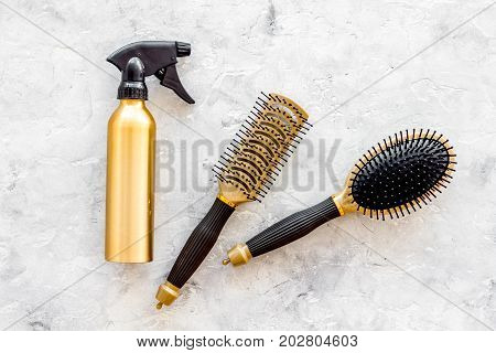 golden combs and spray for hairdresser work set on stone desk background top view