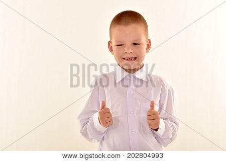 A caucasian elementary age boy with glasses posing in uniform isolated on white background. School and education concept.