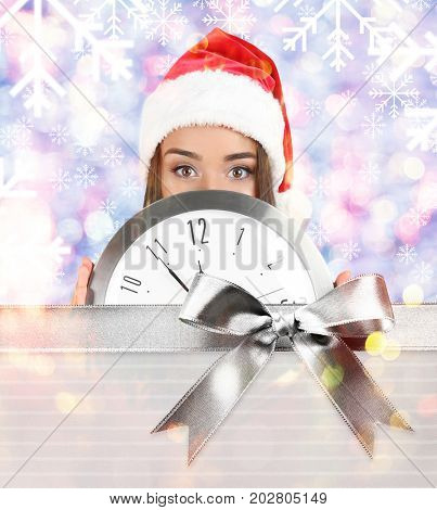 Young woman in Santa hat with clock on blurred lights background. Christmas countdown concept
