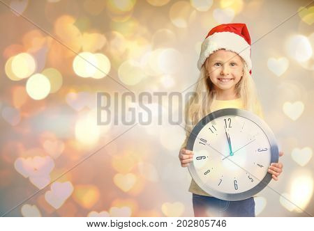 Cute little girl in Santa hat with clock on blurred lights background. Christmas countdown concept