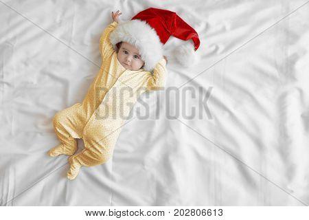 Cute little baby in Santa hat on white sheet