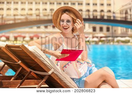 Beautiful young woman reading magazine while relaxing on sun lounger at resort