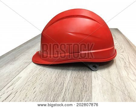 Orange construction helmet lying on a wooden table top isolated on a white background