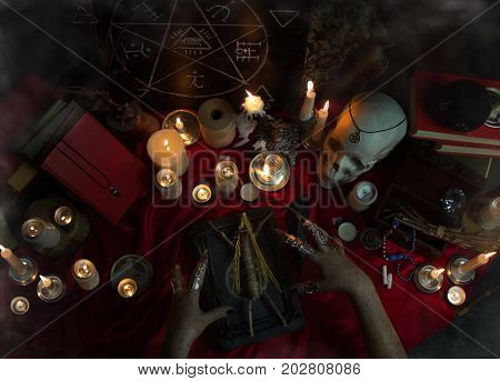 Witchcraft composition with witch's hands carrying out a ritual with Voodoo doll, candles, magic book, magic sphere, crystal, amulets and pentagram symbol. Halloween concept, black magic ritual.
