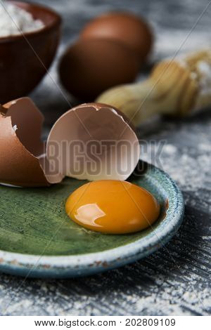 closeup of a cracked egg in a green plate, an earthenware bowl with flour, some whole eggs and a wooden rolling pin on a rustic table sprinkled with flour
