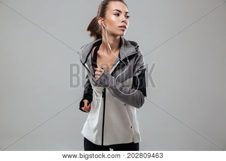 Young female runner in warm clothes running in studio and looking away over gray background