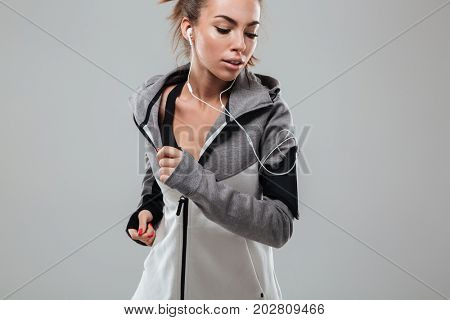 Young female runner in warm clothes running in studio and looking down over gray background
