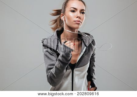 Concentrated female runner in warm clothes running in studio over gray background