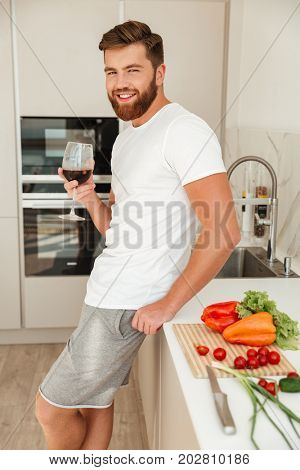 Vertical picture of smiling bearded man standing sideways near the table on kitchen, drinking ice drink and looking at the camera