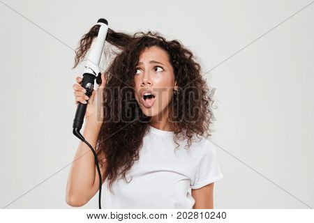 Surprised young brunette woman straighten her hair and looking away over gray background