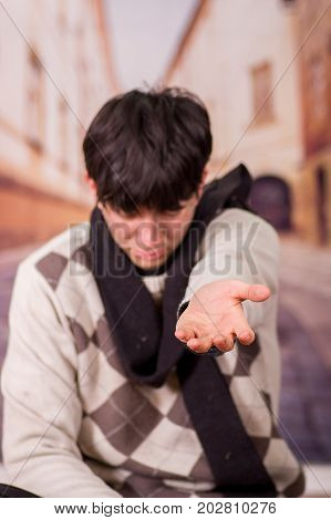 Close up of a homeless young man in the streets, asking for money with one hand, in a blurred background.